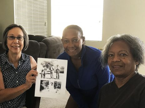 Interview with community consultants, Dr. La Theia Black and Judy Gomez, holding photo of homesteaders in Lanfair in Lanfair, early 1900's