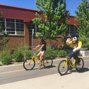 Louie and student riding yellow bikes