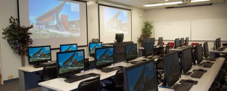 Computer lab with multiple workstations and a projector