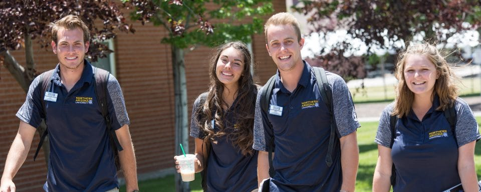NAU representatives walking on campus wearing NAU polos.