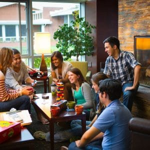 campus residents play jenga and other board games and are laughing together