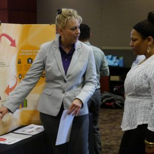 presenter shows poster to attendee at NAU's assessment fair