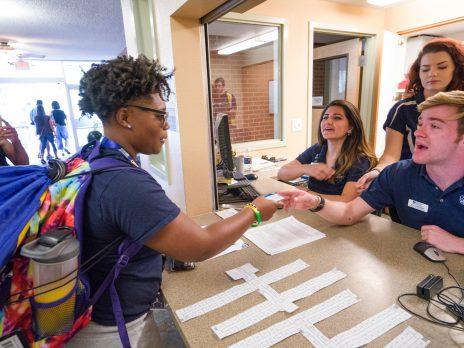 Incoming NAU student is handed over their JacksCard by NAU representative.
