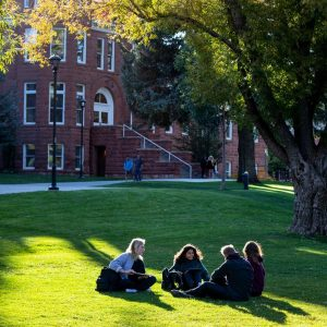 a small group of students studies on the lawn in front of old main