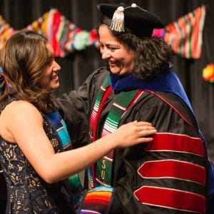 An NAU student and professor hug at the Hispanic Convocation.