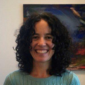 a photo of Megan Gavin wearing a green shirt and smiling at the camera