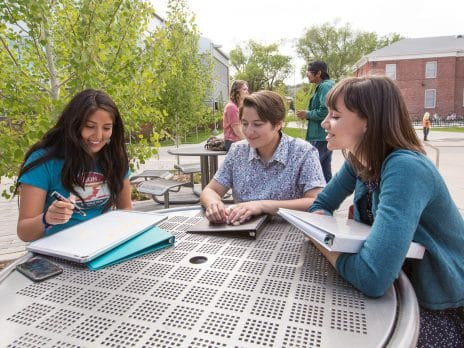 NAU students talking while sitting at a table on campus.