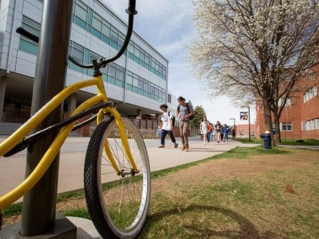 Yellow bike leaning on campus post.
