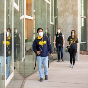 Three masked NAU students walk outside a science building.