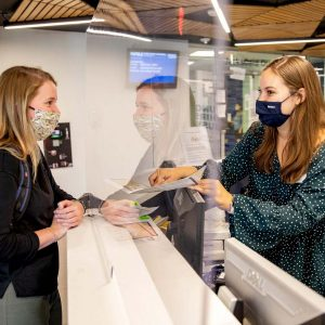NAU students wearning masks at an information counter on campus.