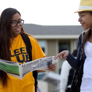 two students reading the lumberjack newspaper