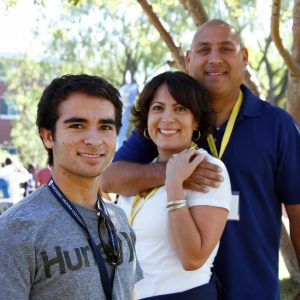male student in focus and his parents behind him smiling and hugging each other at orientation