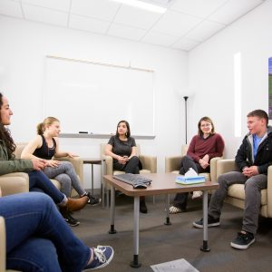 group of students at campus health services talking in a group discussion