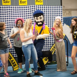 photo of students dressing up and laughing while Louie poses for the photo booth at the Transfer Welcome event