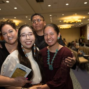 Native student celebrates winning the Gold Axe award and poses with her family