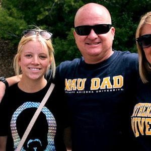 Mom and dad wearing NAU swag hug daughter as she leaves for college