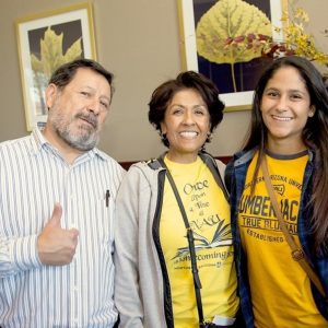 dad gives the camera a thumbs up while he wraps his arm behind his wife and both parents smile with their college-bound daughter
