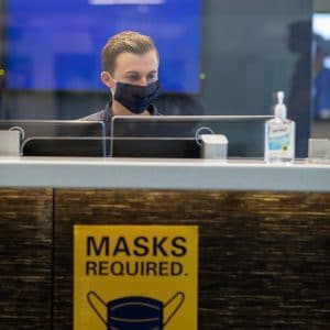A student worker behind plexglass and a masked required sign.