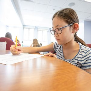 Child drawing picture at NAU table