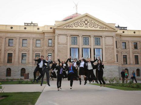 Legislative interns jumping outside of capitol building