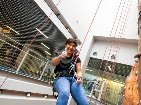 Rec Center women hanging out at climbing wall