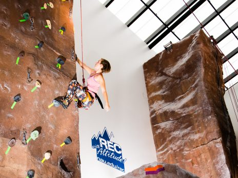 rec center women climbing on rock wall