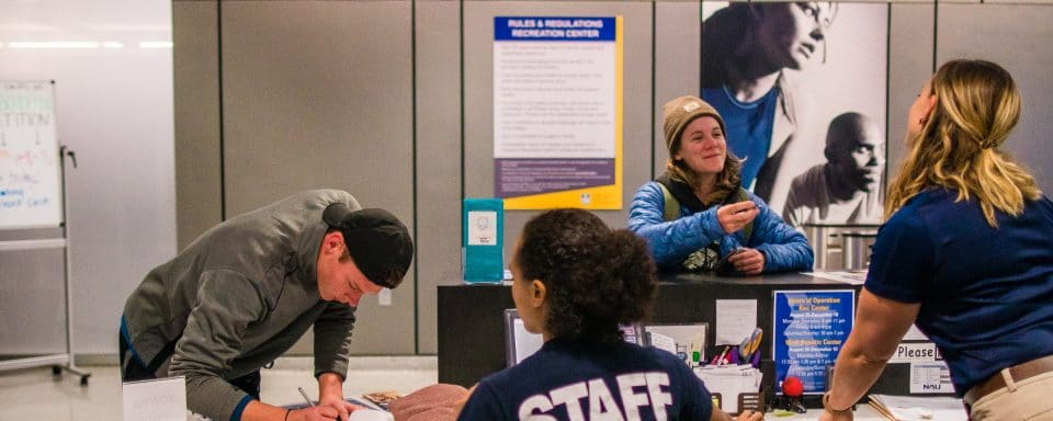 rec center front desk staff helping students