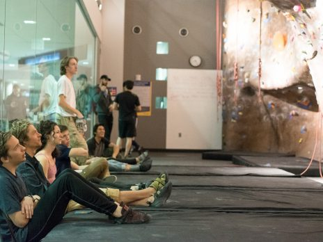 rec center climbing wall student sitting watching climbers