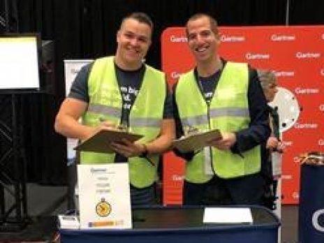 Two smiling Gartner employees behind podium