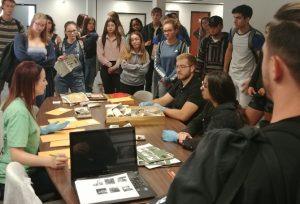 Group of Students stand around table discussing photographs