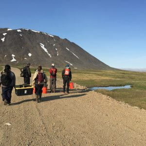 Research team walking down road in Alaska