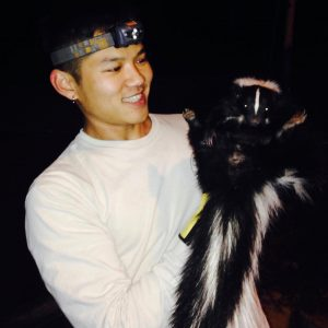 Researcher Victor Zhang holding a skunk