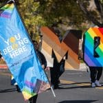 You Belong Here banner being carried in NAU parade next to letters painted with the skin tone rainbow and the pride rainbow