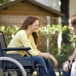 Female student in wheelchair talks to another student outside on a sunny day